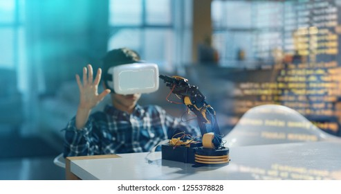 Portrait of boy playing with mechanical arm toy using vr glasses with futuristic augmented reality holograph in living room in slow motion. Concept of innovation technology, family entertainment, game