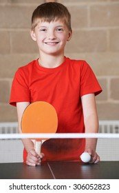 Portrait Of Boy Playing Table Tennis In School Gym