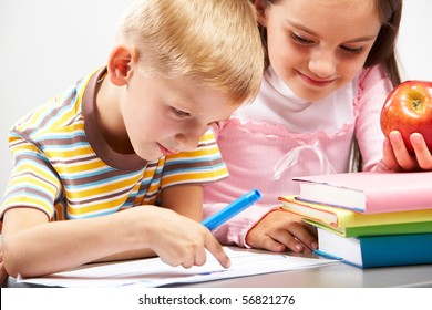 Portrait of boy pointing at paper and  girl with apple