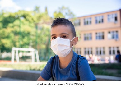 Portrait of a boy with a protective mask on his face sitting in the school yard