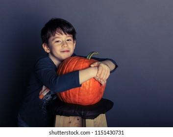 Portrait of a boy with a pumpkin, boy hugging a big pumpkin, a joyful boy on Halloween