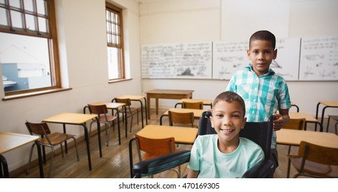 Portrait of boy pushing friend on wheelchair against empty classroom