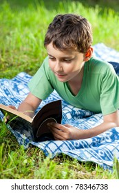 Portrait of a boy reading a book outdoor on the grass