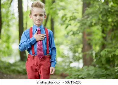 Portrait of boy in red trousers with braces and blue shirt with his hand on chest in summer park.
