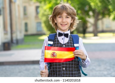 Portrait boy. Schoolboy with the flag of Spain on the background of the school. Student of college. Learn Spanish.