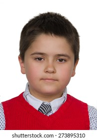 Portrait of a boy of seven years old in a red vest and tie on a white background