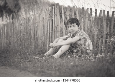 Portrait of a boy sitting on the grass near a wooden fence. Black and white.
