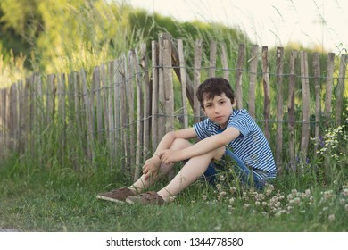 Portrait of a boy sitting on the grass near a wooden fence.