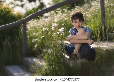 Portrait of a boy sitting on the steps in the park. In the background is a flower field.