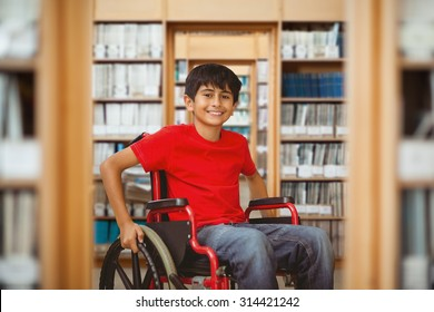 Portrait of boy sitting in wheelchair against library