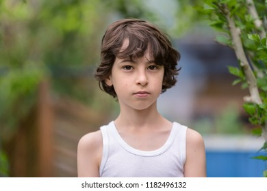 Portrait of a boy in a sleeveless shirt on a nature background. Country style.