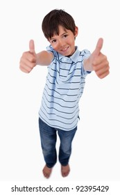Portrait of a boy smiling at the camera with the thumbs up against a white background