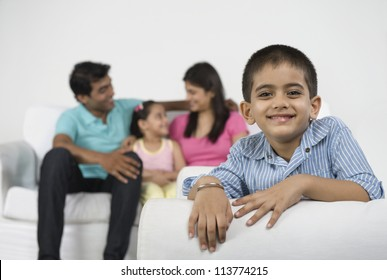Portrait of a boy smiling with his family in the background