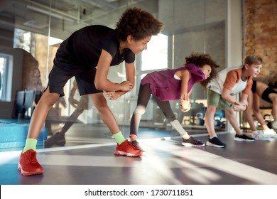 Portrait of a boy smiling while warming up, exercising together with other kids in gym. Sport, healthy lifestyle, active childhood concept. Horizontal shot. Selective focus