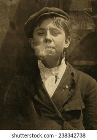 Portrait of a boy smoking a pipe,'A.M. Monday, newsies at Skeeter's branch They were all smoking.', St. Louis, Missouri, photograph by Lewis Wickes Hine, May 9, 1910