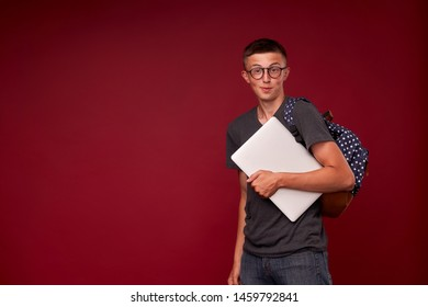 portrait of a boy student with a backpack and laptop in his hands smiling on a red background. funny positive teenager is a high school student with glasses. back to school. copy space
