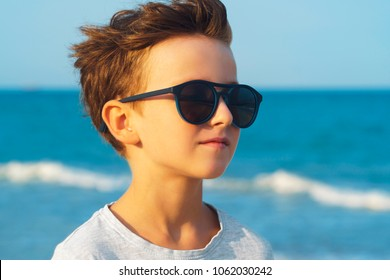 Portrait of a boy in sunglasses by the sea against a blue sky looking into the distance. A small wind blows in the face of the child. Waves at sea