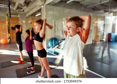 Portrait of boy warming up, exercising with other kids in gym. Stretching on a sunny day. Sport, healthy lifestyle, physical education concept. Horizontal shot. Selective focus