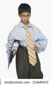 Portrait of a boy wearing oversized clothes and holding a file