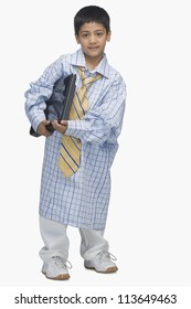 Portrait of a  boy wearing oversized shirt and holding a laptop