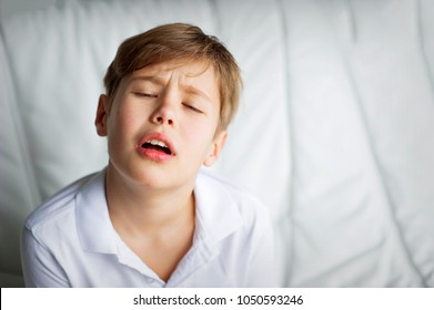 portrait of a boy in a white shirt unhappy face white background