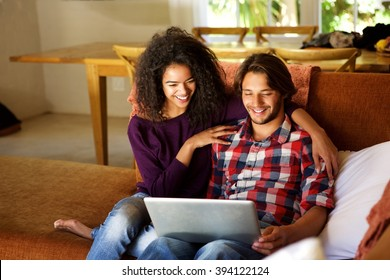 Portrait of boyfriend and girlfriend sitting at home with laptop