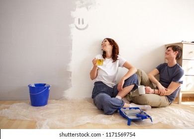 Portrait of boyfriend and girlfriend taking a break from painting their new home