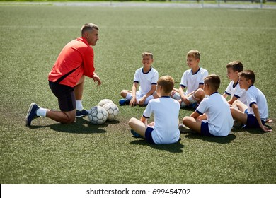 Portrait of boys sitting in front of coach on football field listening to pre game lecture