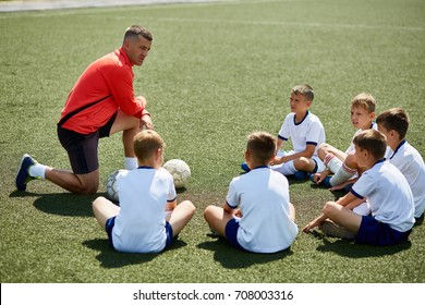 Portrait of boys team sitting in front of coach on football field listening