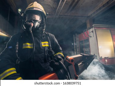 Portrait of a brave firefighter standing confident wearing full protective equipment, turnouts and helmet. Dark background with smoke and blue light.
