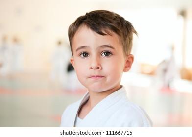 Portrait of brave karate boy training in sport hall