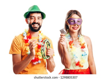 Portrait of brazilian couple wearing carnival costume showing a condom