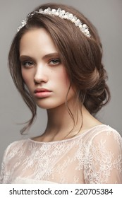 Portrait of the bride with beautiful make up and hairdo on gray background. Wedding trends