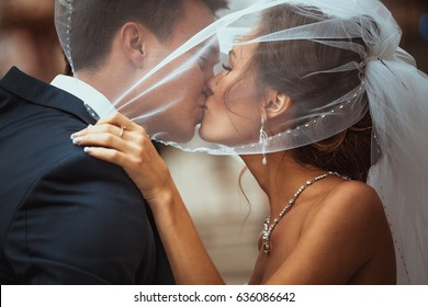 portrait of bride and groom kissing on a background of the city.