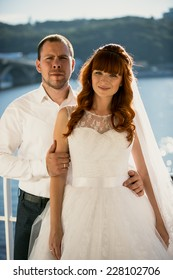 Portrait of bride and groom posing against river at sunny day