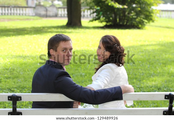 Portrait of bride and groom sitting on bench in park