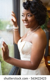 Portrait of a bride looking out the window.
