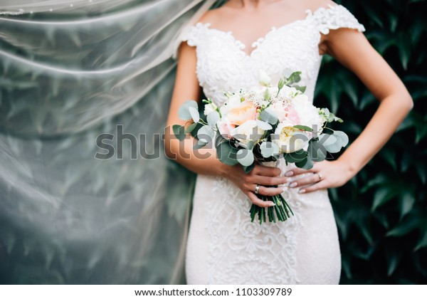 Portrait of a bride in a white dress with a wedding bouquet in the hands, against a background of a green wall