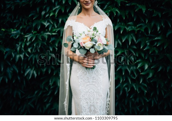 Portrait of a bride in a white dress with a wedding bouquet in the hands, against a background of a green wall of plants