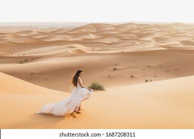 Portrait von Brautfrau in erstaunlichem Hochzeitskleid in der Sahara Wüste, Marokko. Warmes Abendlicht, schöner Pastellton, Sanddünen am Horizont. Naturhintergrund.