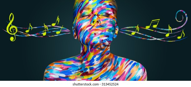 Portrait of the bright beautiful emotional woman with art make-up listen music with notes on dark background