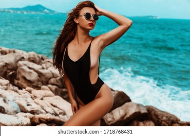 Portrait of a bright beautiful sexy lady in a black bathing suit on a rocky seashore, tanned perfect skin, sunbathing. Summer is calling for travel, vacation on the island