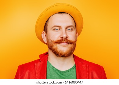 A portrait of a bright man posing in the studio over the yellow background. Men, beauty, colors, fashion.