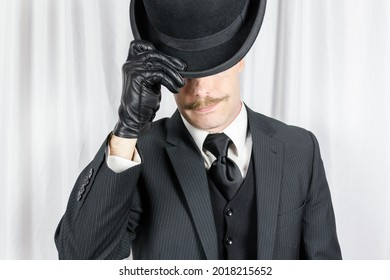 Portrait of British Gentleman in Dark Suit and Leather Gloves Politely Doffing Bowler Hat. Suave Spy Hero with Jaunty Moustache.