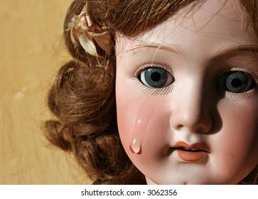Portrait of a broken, antique porcelain doll face with tear.