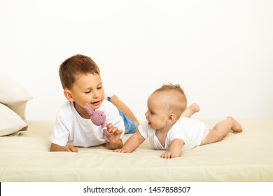 Portrait of brother and baby sister. Two cute children lying on bed. Open-eyed surprised or astonished expression. Brother and sister best friends, happy family and childhood concept.