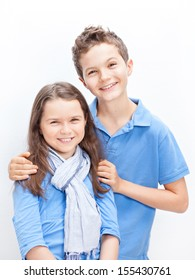 Portrait of a Brother and Sister, both wearing a blue shirt.