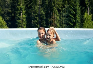 Portrait of brother and sister fooling around in outdoor pool. Children frolic in pool against backdrop of wildlife. Boy and girl having fun, laughing and cuddling