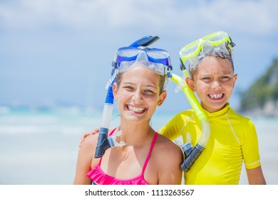 Portrait of Brother and sister in scuba masks playing and having fun on the beach during the hot summer vacation day.