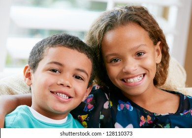Portrait Of Brother And Sister Sitting On Sofa Together